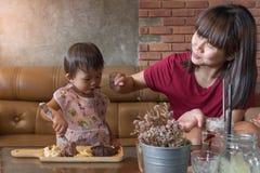 Le bébé et la mère mignons ont plaisir à eatting l'ensemble de lave de chocolat Image stock