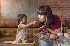 Le bébé et la mère mignons ont plaisir à eatting l'ensemble de lave de chocolat Images stock