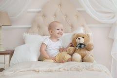 Le bébé et le nounours concernent le lit dans la chambre à coucher sur le réveil Images stock