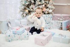 Le bébé et le sort mignons de cadeaux de Noël s'approchent de l'arbre Photographie stock