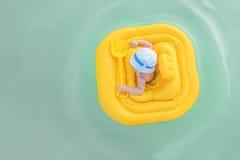Le bébé flotte dans un radeau gonflable jaune Fond avec l'espace de copie Photographie stock