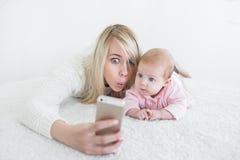 Le bébé font le selfie au téléphone portable Photographie stock libre de droits