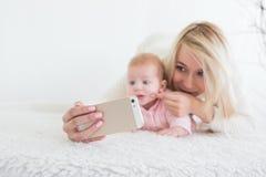 Le bébé font le selfie au téléphone portable Photo stock