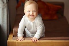 Le bébé gai avec le sourire amical mignon se tient sur le divan Images libres de droits
