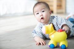 Le bébé garçon asiatique jouant le cheval joue sur le plancher photo libre de droits