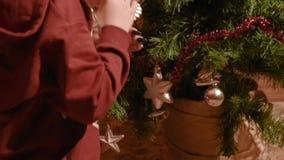 Le bébé garçon avec la maman habillent l'arbre de Noël de jouets à la maison banque de vidéos