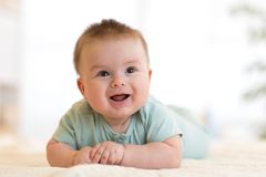 Le bébé garçon caucasien heureux mignon se trouve souriant sur le lit Image stock