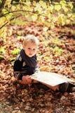 Le bébé garçon d'automne envisagent de lire un livre sous un arbre Photographie stock
