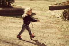 Le bébé garçon dans la veste bleue et les jeans marchent avec le bâton photographie stock