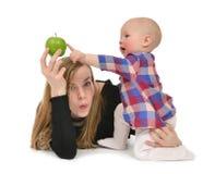 Le bébé garçon de mère et d'enfant badinent avec la pomme verte Photos libres de droits