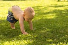Le bébé garçon drôle font ses premiers pas extérieur sur la pelouse image stock