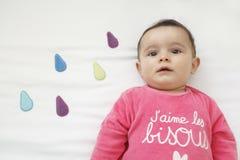 Le bébé garçon en bonne santé sur son lit avec la pluie colorée se laisse tomber sur le blan Photos libres de droits