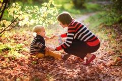 Le bébé garçon et la mère d'automne envisagent de lire un livre sous un arbre Image libre de droits