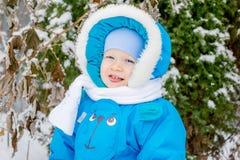 Le bébé garçon heureux est heureux de neiger Photographie stock