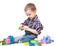 Le bébé garçon jouant avec des blocs joue sur le fond blanc photographie stock