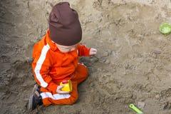Le bébé garçon joue dans le bac à sable Photo libre de droits