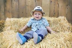 Le bébé garçon joue sur une balle de paille Image libre de droits