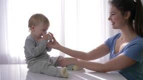 Le bébé garçon mignon avec des larmes dans les yeux buvant l'eau pure du verre des mains de mère et se réjouit dans l'extinction  banque de vidéos