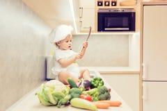 Le bébé garçon s'asseyant parmi des légumes dans la cuisine et se prépare à la cuisson photos libres de droits