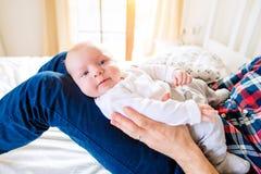Le bébé garçon s'est tenu par son père s'asseyant sur le lit Photo libre de droits