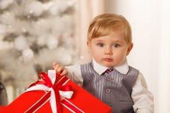 Le bébé garçon tient un grand boîte-cadeau rouge images stock