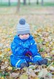 Le bébé garçon triste s'asseyant sur le jaune part en automne Photographie stock libre de droits