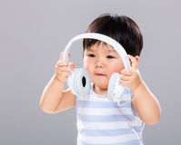 Le bébé garçon veulent écouter musique utilisant l'écouteur Photos stock