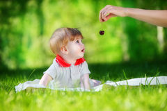 Le bébé heureux ont l'amusement dans le parc sur un pré ensoleillé avec des cerises Image libre de droits
