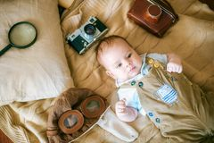 Le bébé heureux se trouve sur une couverture de maison avec des livres, un rétro appareil-photo et un casque pilote du ` s à la m Photos stock