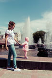 Le bébé joue à la fontaine Photo stock