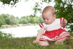 Le bébé joue avec l'herbe photographie stock