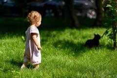 Le bébé joue avec un chat en parc Photographie stock