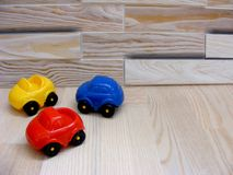 Le bébé joue des voitures de jaune de rouge bleu sur le fond en bois image libre de droits