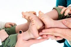 Le bébé jumelle des pieds dans des mains de parents Photos libres de droits