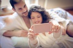 Le bébé laisse prendre une photo de nous Dans des couples de jeunes d'amour Images stock
