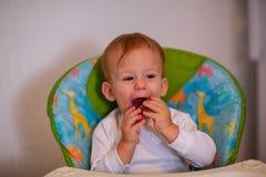 Le bébé malpropre de sourire aime manger photographie stock