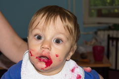 Le bébé malpropre et sale mange le casse-croûte Photo stock