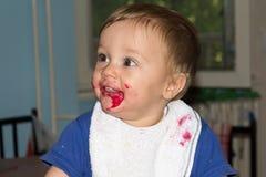 Le bébé malpropre et sale mange le casse-croûte Photographie stock