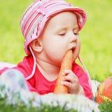 Le bébé mange des carottes Image stock