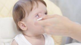 Le bébé mange du gruau de la cuillère, crache et sourit se reposant sur le highchair dans la cuisine banque de vidéos