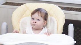 Le bébé mange du gruau de la cuillère, crache et sourit se reposant sur le highchair dans la cuisine clips vidéos