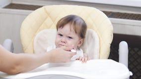 Le bébé mange du gruau de la cuillère, crache et sourit se reposant sur le highchair dans la cuisine photo libre de droits