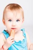 Le bébé mangent le biscuit images stock