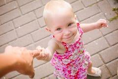 Le bébé marche tenant le doigt de parents, amour, appui, concept de confiance Photographie stock