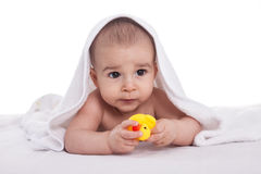 Le bébé mignon apprécient sous la serviette blanche avec des jouets de bain, d'isolement Images stock