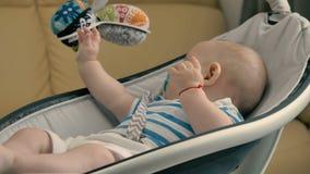 Le bébé mignon avec le simulacre joue avec des jouets dans le berceau clips vidéos