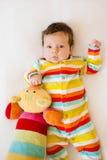 Le bébé mignon avec les pyjamas colorés rayés et un chat jouent le mensonge sur le lit Photos libres de droits