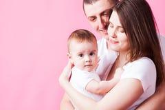 Le bébé mignon dans le ` s de parent arme regarder l'appareil-photo Photographie stock libre de droits