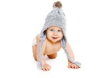 Le bébé mignon de portrait dans le gris a tricoté des rampements de chapeau sur le blanc photographie stock libre de droits