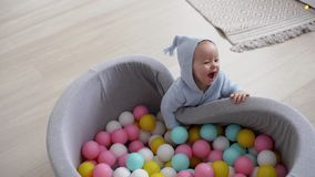 Le bébé mignon heureux avec un sourire essaye d'entrer dans la piscine des boules colorées banque de vidéos
